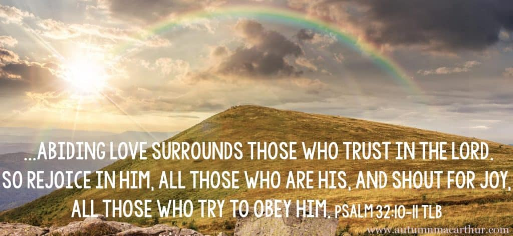 Image of rainbow on hilltop with Bible verse Psalm 32:10-11 by inspirational romance author Autumn Macarthur for Inspy Romance